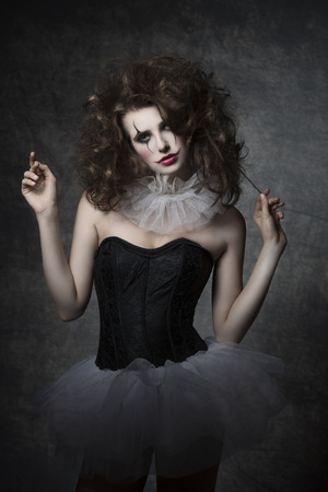 horror: masquerade woman with vintage dancer dress, sad clown make-up and uncombed hair. Romantic fashion portrait Stock Photo