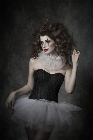 mujeres tristes: hermosa niña morena con triste mascarada bailarina payaso, posando con tutú vintage, payaso maquillaje y el pelo despeinado. Ambiente retro Foto de archivo