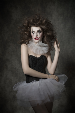 cute woman with crazy  hair style posing with clown make-up and vintage tutu. Bizzarre romantic masquerade photo
