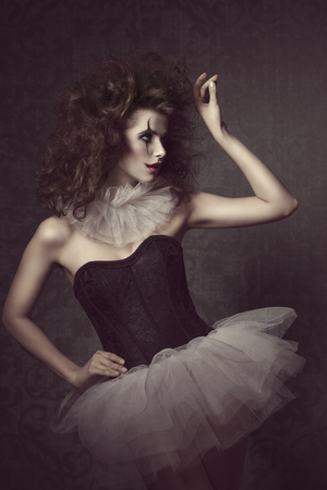 stunning vintage masquerade portrait of sensual brunette woman with vintage gothic tutu, clown make-up and crazy hair-style photo