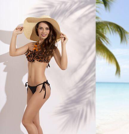 posa sexy: moda sparare estate di molto sexy donna bruna con corpo perfetto, grande cappello di paglia in testa, bikini di modo e la collana. In posa sexy guardando a porte chiuse Archivio Fotografico