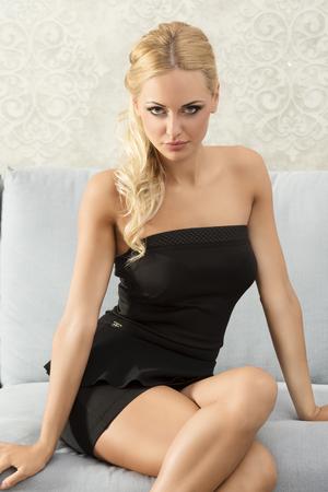 femme noire nue: élégante jeune fille blonde, de noir, assise sur le canapé, posant et en regardant la caméra. elle a do de cheveux Banque d'images
