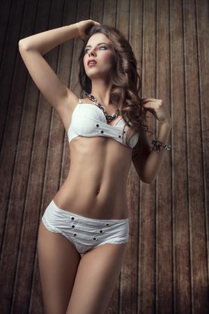 hot girl nude: fashion summer shot of sensual brunette woman with perfect body, long hair, stylish bikini and jewellery Stock Photo