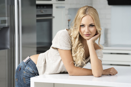 sexy housewife: pretty young girl posing in her home kitchen , looking in camera , caucasion blond style Stock Photo