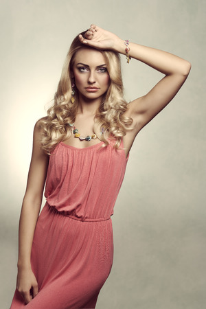 vintage version of summer blond young woman with colored dress and jewelery. She is posing on grunge background photo