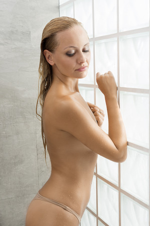 aqua naked: Beautiful, natural, fresh, healthy female with blonde hair and natural make up is standing in the shower, her body is wet, she is looking down.