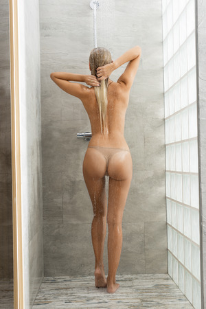 aqua naked: Pretty, healthy, sexy, feresh woman with long blonde hair is taking a shower, she is standing back of. She is holding her hair.