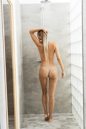 aqua naked: Beautiful, natural, fresh, healthy female is standing in the shower. She has got long, blonde hair. Water is splashing on her body.