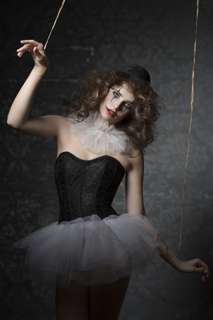 puppet woman: pretty woman masquerade like bizarre gothic puppet with tutu, bowler hat and clown make-up. Uncombed hair, dark atmosphere
