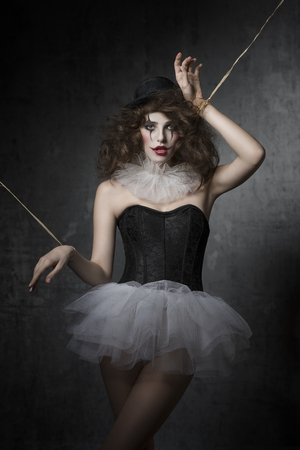 puppet woman: bizarre fashion portrait of brunette girl with gothic puppet costume. Wearing tutu, bowler hat and clown make-up. Uncombed hair, dark atmosphere