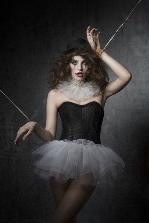 uncombed: bizarre fashion portrait of brunette girl with gothic puppet costume. Wearing tutu, bowler hat and clown make-up. Uncombed hair, dark atmosphere