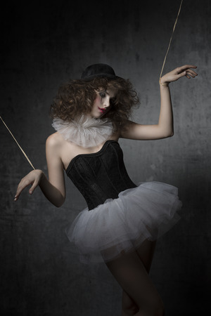 uncombed: gothic fashion shoot with uncombed brunette wearing like gothic puppet with tutu, bowler hat and clown make-up.