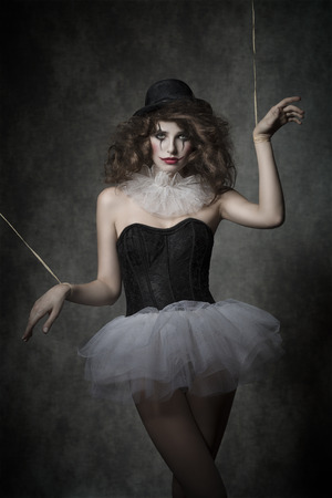 uncombed: girl in creative fashion shoot with gothic atmosphere. She is wearing like horror puppet with vintage tutu, bowler hat and clown make-up.