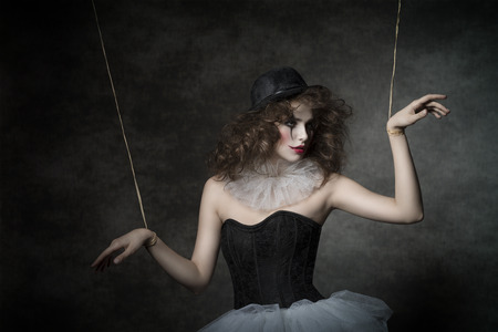 puppet woman: uncombed sensual woman with gothic puppet costume, uncombed hair and clown make-up. She wearing vintage tutu and bowler
