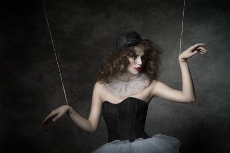 uncombed sensuele vrouw met gotische marionet kostuum, ongekamde haren en clown make-up. Ze dragen vintage tutu en bowler Stockfoto