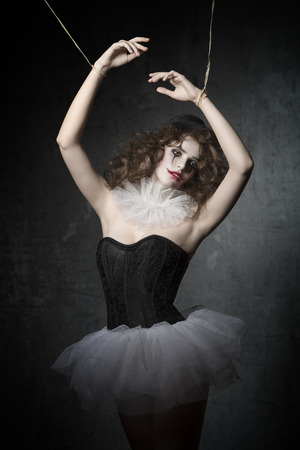 girl with gothic puppet dancer costume and sad clown make-up. She wearing vintage tutu and bowler hat. in marionette pose