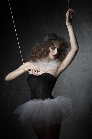 brunette girl posing like marionette dancer with gothic style. She, with clown make-up, wearing vintage tutu and bowler hat. photo