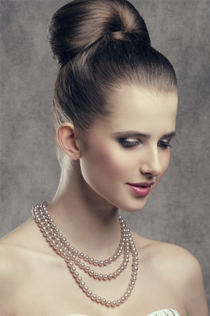 pearl necklace: close-up portrait of fine brunette woman with elegant hair-style, stylish make-up and precious pearl necklace