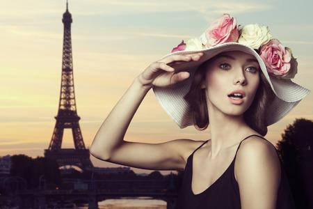 일부 화려한 장미와 세련 된 메이크업 큰 꽃 모자와 아주 예쁜 갈색 머리 여자의 근접 촬영. 놀란 표정으로 포즈. 그녀는 파리에있다.