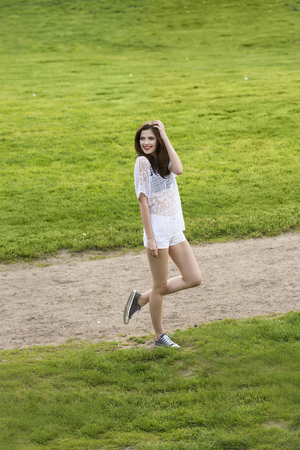 casual fashion: Casual fashion girl , near a green grass , outside in the park wearing a white shirt and short she is looking on one side smiling