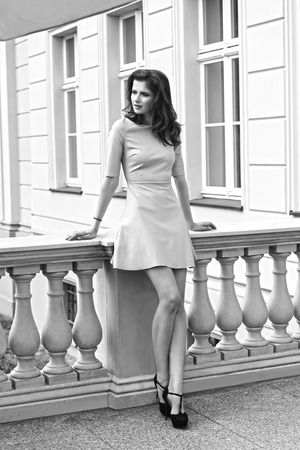 black lady: charming brunette girl posing in fashion outdoor shoot with trendy pink dress and heels.black and white portrait