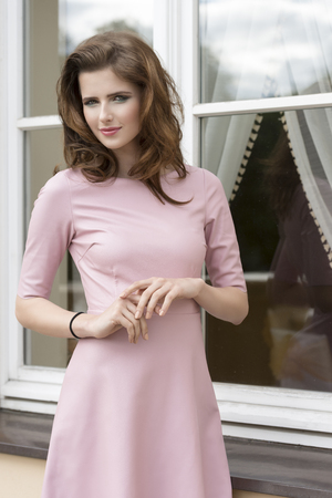 fashion shoot of very pretty brunette woman with natural hair-style, pink dress and stylish make-up, posing outdoor near window photo
