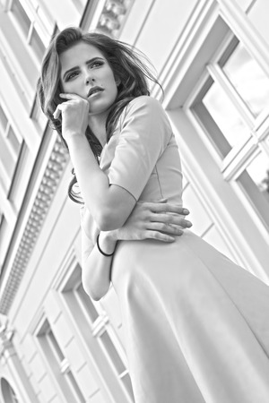 Black and white fashion portrait of a young pretty girl with old building in background , she is looking away photo