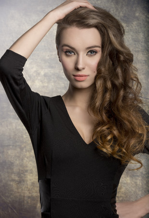 femme brune sexy: la mode féminine brune posant avec une robe noire mignon, élégant maquillage et de longs cheveux ondulés brillant. Charmante expression regardant dans la caméra