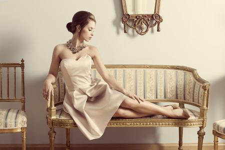 interieur portret van brunette elegant meisje dat op retro sofa in aristocratische kamer. Het dragen van roze jurk, kostbare sieraden en klassieke kapsel. Luxe sfeer