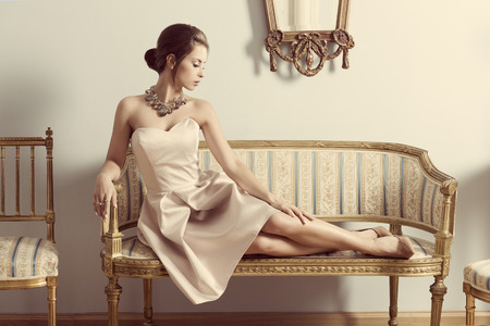 vintage dress: interior portrait of brunette elegant girl lying on retro sofa in aristocratic room. Wearing pink dress, precious jewellery and classic hair-style. Luxury atmosphere