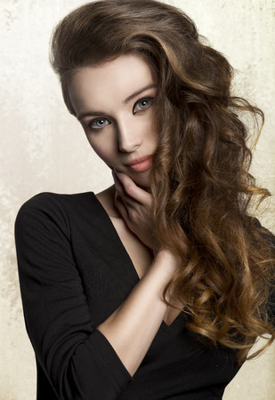 black hair: close-up portrait of very pretty young woman with nice make-up and long volume wavy hair. Wearing black  dress