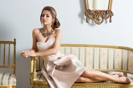aristocratic: Rich woman with aristocratic style lying on antique sofa in aristocratic room and looking in camera. Wearing elegant pink dress and precious necklace.