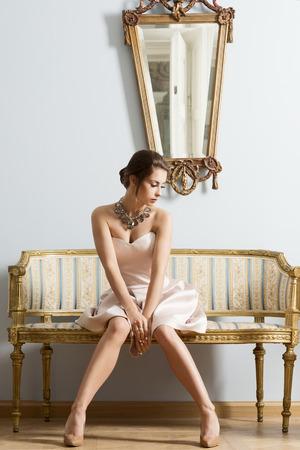 muebles antiguos: Mujer morena sensual con elegante vestido y peinado clásico sentado en el sofá de la vendimia en la habitación aristocrática. Interior retrato de la moda de lujo Foto de archivo