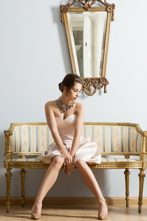 sensual: Sensual brunette woman with elegant dress and classic hair-style sitting on vintage sofa in aristocratic room. Interior luxury fashion portrait