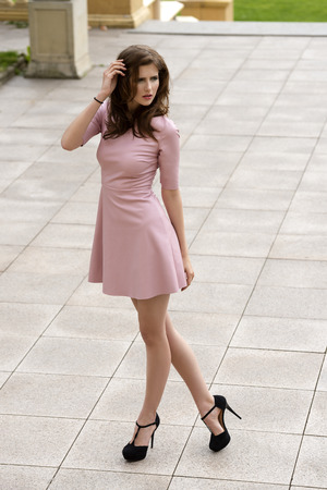 sexy pink: outside portrait of elegant brunette female wearing sexy pink dress and cute black heels. Natural hair-style