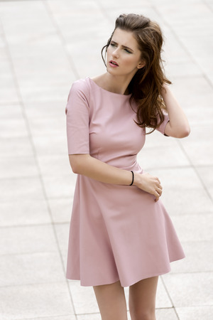 sunny outdoor fashion shot of charming brunette girl with elegant pink dress in natural pose Standard-Bild
