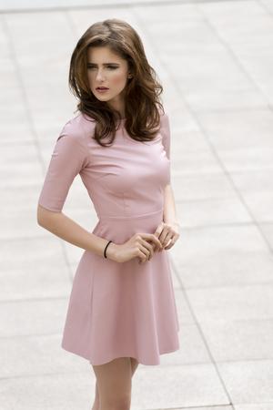 sensual mujer joven con el pelo largo de color marrón natural y elegante vestido rosa posando en sesión de moda al aire libre