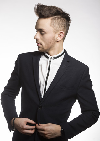 men standing: fashion young model male , wearing a trendy black suit , with white shirt he is looking on one side