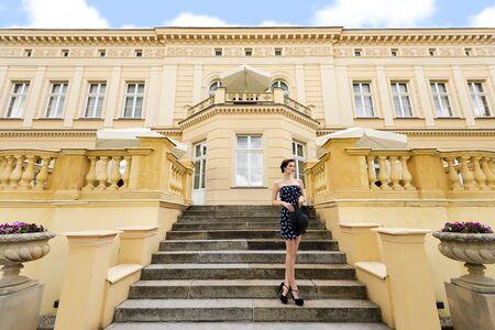 escalera: princesa muy linda en un elegante vestido azul con sombrero, de pie en las escaleras de la vieja Bulding, fuera y mirando lejos