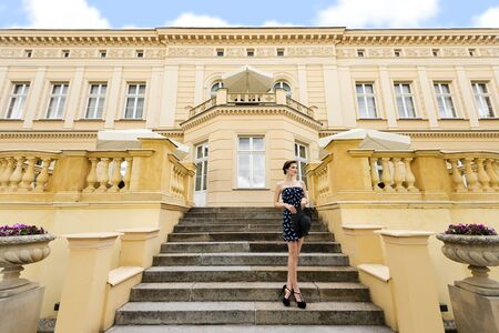 stairs: very cute princess in elegant blue dress with hat , standing on stairs of old bulding , outside and looking far away