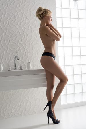 sexy nackte frau: blonde Frau mit perfekten nackten Körper Einschalten Profil, stehend in der Nähe von Bad elegant modernen Waschbecken, trägt nur schwarze Höschen und Fersen und bedeckt ihre nackte Brust