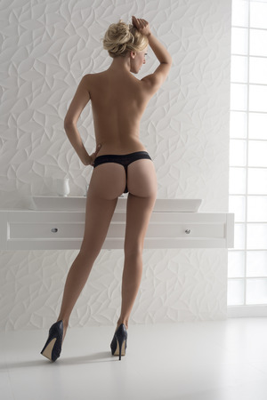 interior portrait of sensual naked blonde woman, wearing black panties and stylish heels, turned on her back and posing near modern washbasin in bathroom