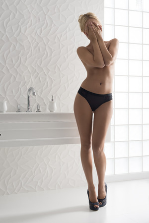 woman naked body: sensual woman in modern bathroom with naked perfect body wearing only black panties and heels. Posing near washbasin and covering her face and her naked breast