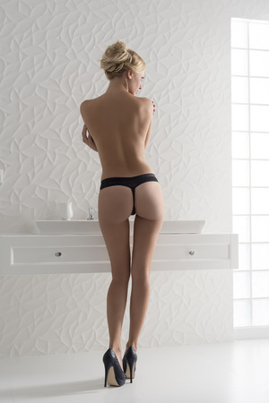 nude women: sexy blonde girl nude with only panties and heels posing in bathroom near modern washbasin turned on her back