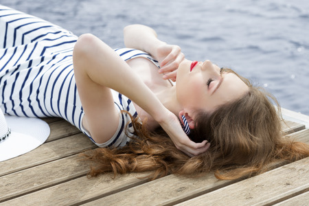 fashion woman lying relaxing on wood jetty near blue sea water in summertime. Wearing trendy summer striped dress.