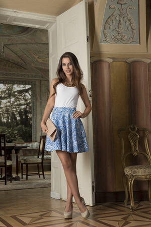 cute fashion girl with trendy summer elegant clothes and heels posing in old room with ancient furniture. Luxury antique palace