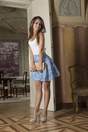 summer palace: smiling beautiful brunette model with long hair and elegant summer clothes and heels, posing in interior with aristocratic ancient furniture. Fashion portrait in ancient palace.