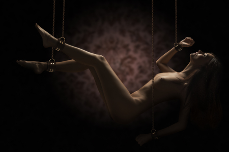 beautiful naked woman in artistic images , she hung up , by golden chains , closed eyes Stock Photo