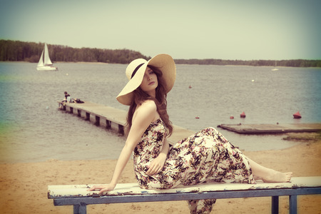 pretty woman ,  posing on the beach near a lake , she is wearing floral dress and summer hat , water in background.vintage color