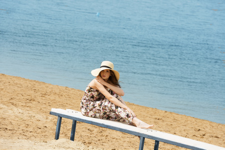 woman dress: romantic cute woman , sitting in the beach , she is wearing floral dress hat , she enjoy the sun in the beautiful day, she is resting